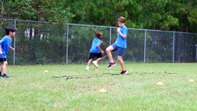 children's soccer team players run through cones and ladder. - sports training drill stock videos & royalty-free footage