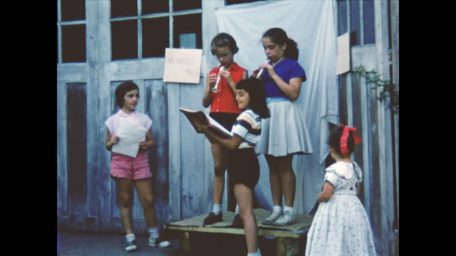 A children's talent show. Girls play their flutes out in their backyard.