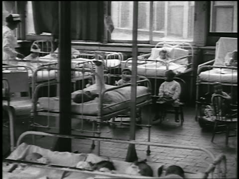 b/w 1920 pan children's ward in hospital / detroit, michigan / newsreel - 1920 stock-videos und b-roll-filmmaterial
