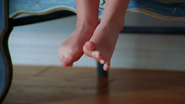 a child's bare feet hang over a chair. - chair stock videos & royalty-free footage