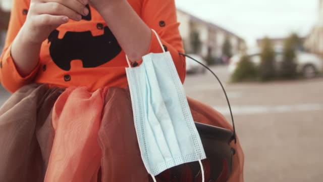 kinderkorb mit süßigkeiten und schützender gesichtsmaske an halloween im herbst - halloween stock-videos und b-roll-filmmaterial
