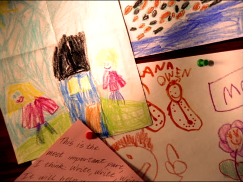 A child's crayon drawings cover a bulletin board.
