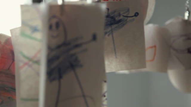 CU R/F Child's drawings hanging in room / Brooklyn, New York City, USA