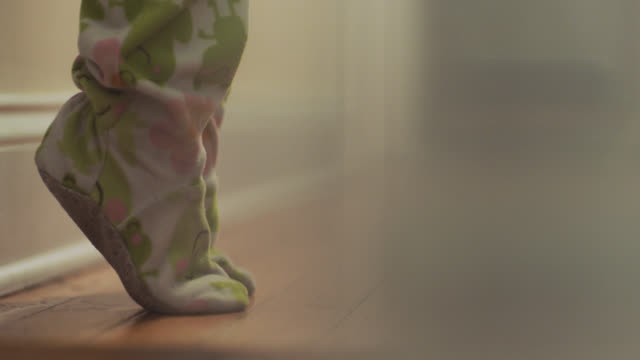 cu. childs feet stand on tip toes in footie pajamas. - auf den zehenspitzen stock-videos und b-roll-filmmaterial