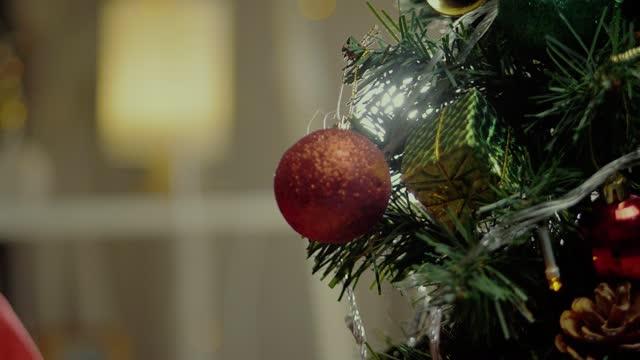 vídeos y material grabado en eventos de stock de la mano del niño decorando el árbol de navidad en la noche en casa, concepto de vacaciones. - cinta de cabeza