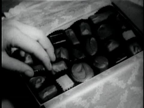 b/w cu child's hand selecting piece of chocolate from box / usa - pampering stock videos & royalty-free footage