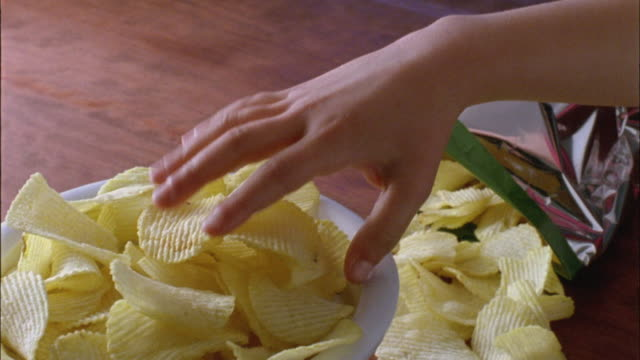 cu, child's (6-7) hand taking potato chips from bowl - unhealthy eating 個影片檔及 b 捲影像