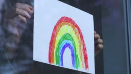 Child's rainbow picture being placed in a window.
