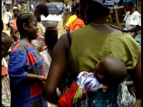 new leads; lib ivory coast: people in market tomatoes displayed covered with flies girl fanning tomatoes with leaf to keep off flies people in market - côte d'ivoire stock videos & royalty-free footage