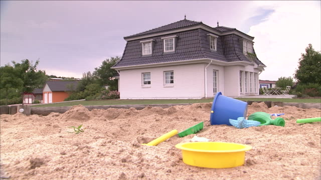 a child's toys lie in a sandbox near a house with a mansard roof. - sand pit stock videos and b-roll footage