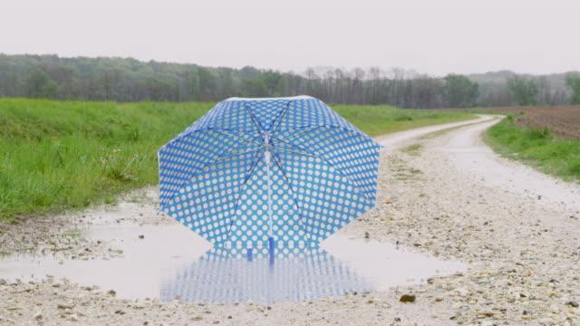 vídeos de stock e filmes b-roll de slo mo ds child's umbrella in a muddy puddle - chapéu