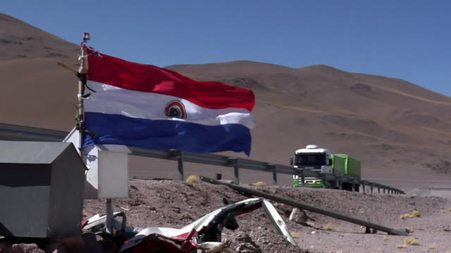ms chilean flag flapping in desert landscape, truck passing in background, san pedro de atacama, el loa, chile - san pedro de atacama stock videos & royalty-free footage