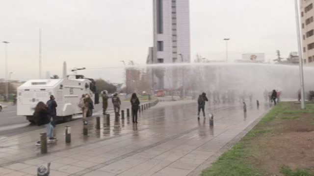 chilean police use a water cannon to disperse demonstrators who hold up banners and wave mapuche indigenous flags in front of santiago's plaza... - water cannon stock videos & royalty-free footage