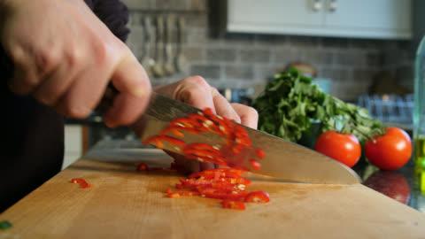 vidéos et rushes de chili pepper is finely sliced with kitchen knife - aliment en portion