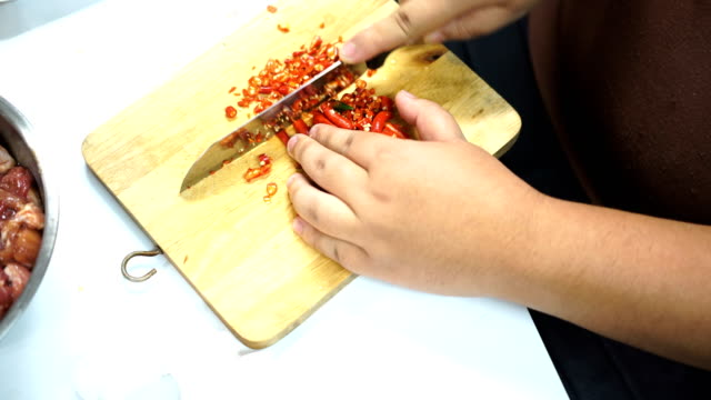 chili peppers sliced on wooden chopping broad - peperone video stock e b–roll