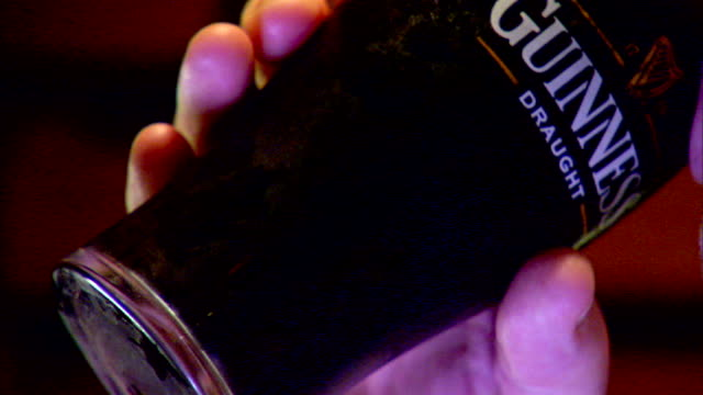 cu chilled glass full of guinness stout draught beer being lifted by male hand out/in focus glass w/ beer being chugged down downing in one long... - foam hand stock videos and b-roll footage