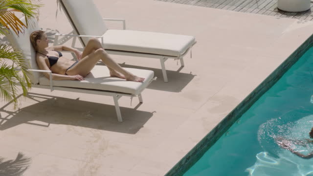 chilling by the pool - bikinioberteil stock-videos und b-roll-filmmaterial