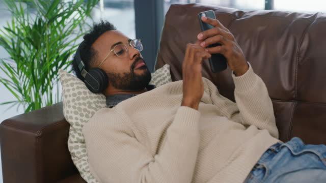 vídeos de stock, filmes e b-roll de relaxando com boa música - sofá