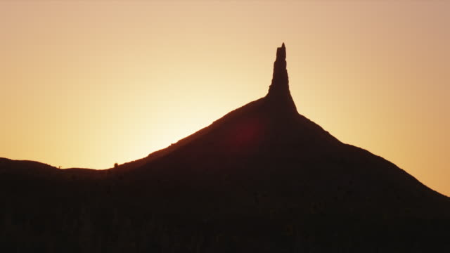 Chimney Rock silhouetted against sunset with clear skies