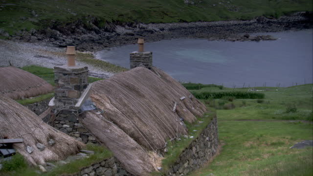 Chimneys poke out of thatched roofs in Blackhouse Village. Available in HD.