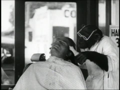 vidéos et rushes de b/w 1939 chimpanzee barber putting aftershave on man + then drinking it / short - barber shop