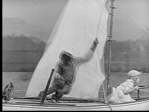 vídeos de stock, filmes e b-roll de 1924 b/w montage ws chimpanzee holding onto sailboat pole driven by girl (alice waldron) as wind machine blows / ms men tossing paper in front of large fan / chimpanzee losing his grip on pole / usa - ator