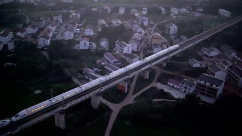 stockvideo's en b-roll-footage met china bullet train on move in fuzhou city aerial view - veiligheidshek