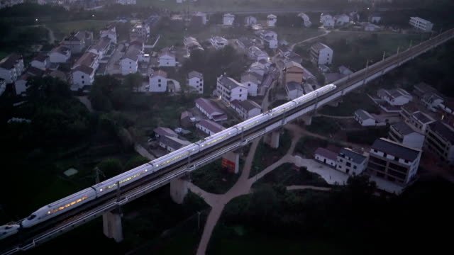 china bullet train on move in fuzhou city aerial view - velocità video stock e b–roll
