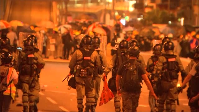 vídeos y material grabado en eventos de stock de china calls for hong kong protesters to be swiftly punished; china: hong kong: ext at night riot police walking away along road. - channel 4 news