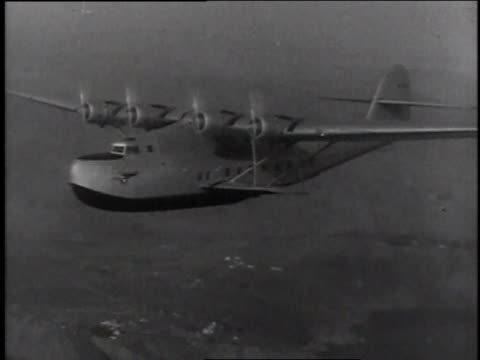 China Clipper in flight / pilot behind controls / interior of plane with radioman in headphones