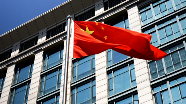 China flag waving against business building