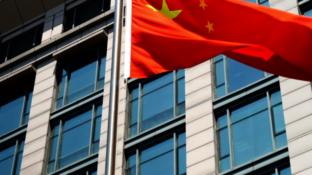 china flag waving against business building - chinese flag stock videos and b-roll footage