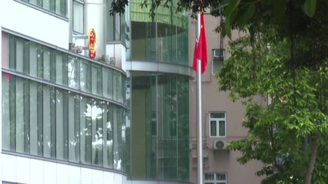 china opens a new office for its intelligence agents to operate openly in hong kong under a new security law, raising the chinese flag in front of a... - hong kong flag stock videos & royalty-free footage