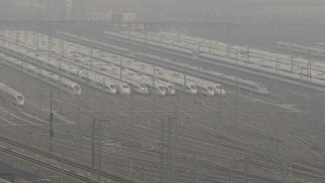 china railway high-speed trains, operated by china railway corp., sit in a train yard shrouded in haze on the outskirts of shanghai, china, on... - high speed train stock videos & royalty-free footage