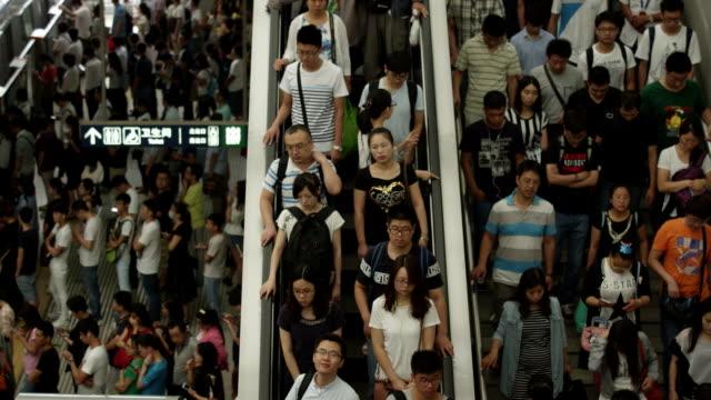 vídeos de stock e filmes b-roll de china subway : wide shot of people get off on an escalator - chinês
