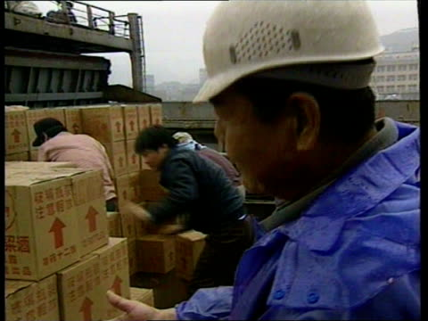 china / taiwan tensions:; taiwan: keelung: ext lorry past at harbour with container ship in b/g container lowered onto ship lms boxes of wine... - lowering stock videos & royalty-free footage