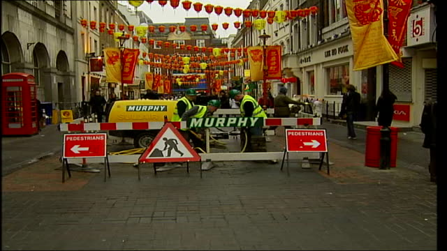 china town undergoes regeneration; england: london: china town: ext gvs workmen digging up pedestrian road in china town gerrard street' sign red &... - all around competition stock videos & royalty-free footage