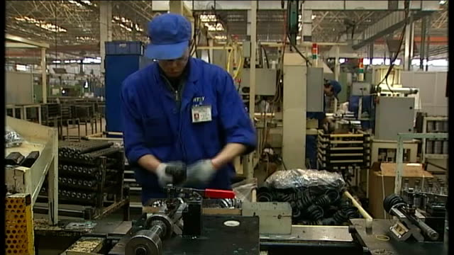 vidéos et rushes de china us relationship worker assembling car parts with machinery gvs chinese workers in blue overalls at work in factory - salopette