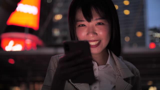 vídeos de stock e filmes b-roll de china woman using smart phone at night - em frente de