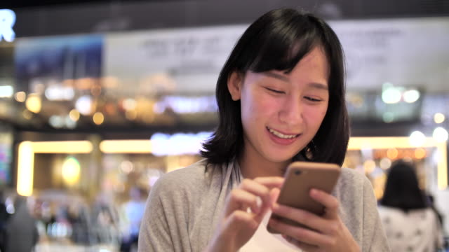china frau mit smartphone in der nacht - china east asia stock-videos und b-roll-filmmaterial