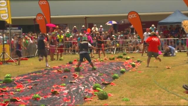 vidéos et rushes de chinchilla melon festival - contestants slide and ski on plastic slide using watermelons as skis - concurrent