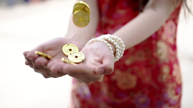 """chinese ancient gold coin floating to hands of young woman wearing traditional chinese dress , the chinese word on gold means """"money is coming"""", happy chinese new year concept. - dress stock videos & royalty-free footage"""