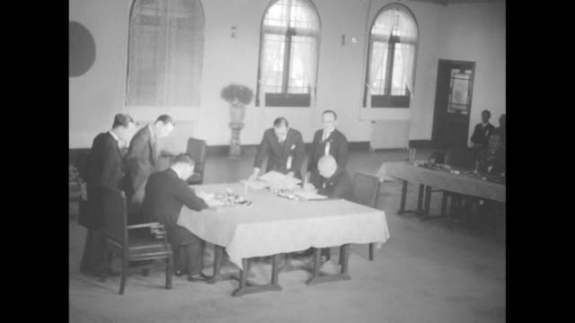 chinese and japanese delegates sit at table, signing the china-japan treaty on basic relations / japanese delegate signs treaty / chinese delegate... - 大使点の映像素材/bロール