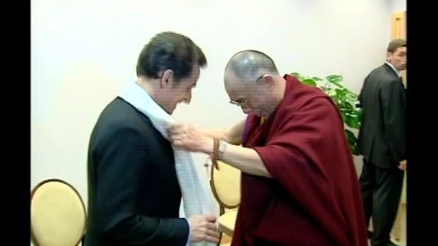 chinese art dealer refuses to pay for bronze sculptures; 6.12.2008 poland: gdansk: int the dalai lama placing white robe around neck of nicolas... - positioning stock videos & royalty-free footage