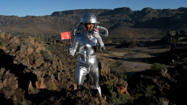 vídeos de stock e filmes b-roll de chinese astronaut plants a flag on another planet - extraterrestre