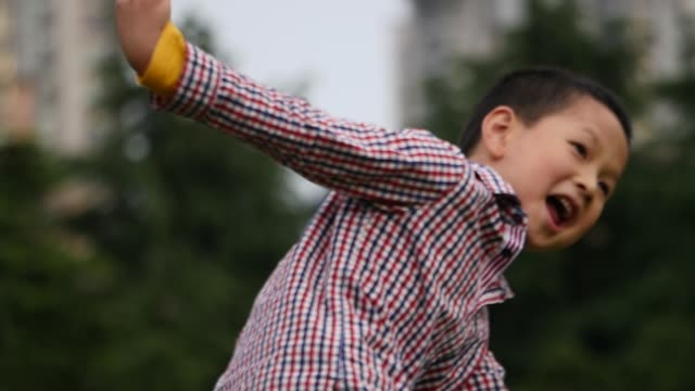 chinese boy playing in the park,flying the toy plane - 2005 stock videos and b-roll footage