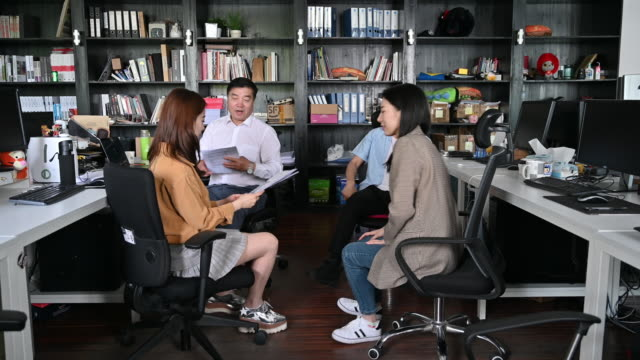 chinese business colleagues in impromptu office meeting - mixed age range stock videos & royalty-free footage