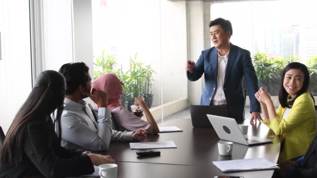 chinese business manager explaining to colleagues in meeting - chinese ethnicity stock videos & royalty-free footage