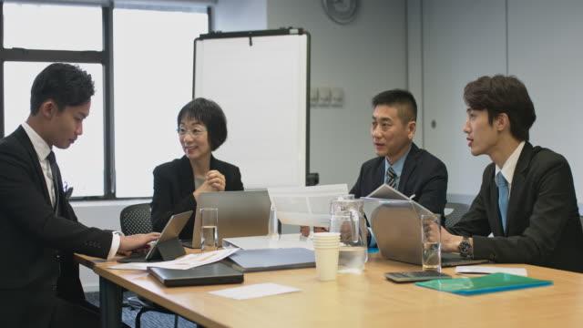 オフィスでのビジネス会議で中国の実業家 - 4人点の映像素材/bロール