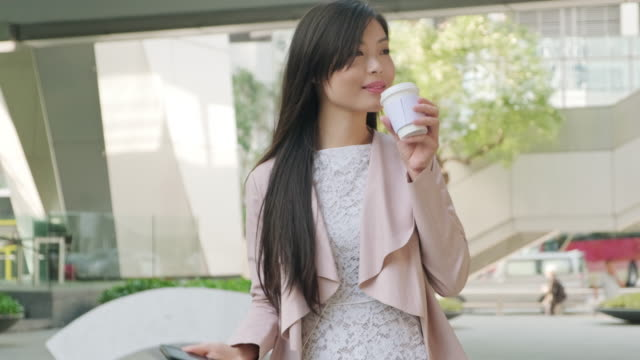 chinese business woman holding a cup of tea outdoors - chinese tea cup stock videos and b-roll footage